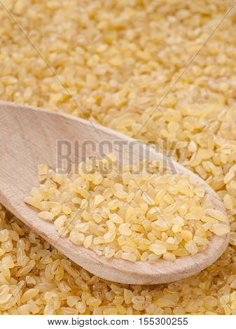 bulgur in wooden spoon close up. Vertical with copy space