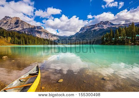 In shallow water the small boat is moored. The concept of eco-tourism and active tourism. The mountain Emerald lake Yoho National Park