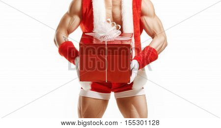 Muscular Santa Claus holding a Christmas present in red box. Happy fitness Santa holding a red box. Sexy Santa Claus. Christmas present in red box.