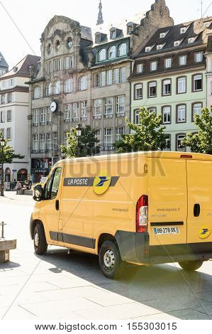 STRASBOURG FRANCE - JUN 24 2016: Postal delivery van in central Square Place Kleber early in the morning delivering mail. La Poste is France's leading employer with a total workforce of 300000 working in postal shipping and banking branches
