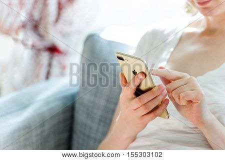 PARIS FRANCE - SEP 29 2016: New Apple iPhone 7 plus display in woman's hands - she is testing the camera and overall presentation sitting on the couch in home environment. New Apple iPhone tends to become one of the most popular smart phones in the world
