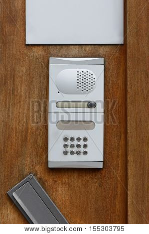 image of intercom on a wooden door close-up