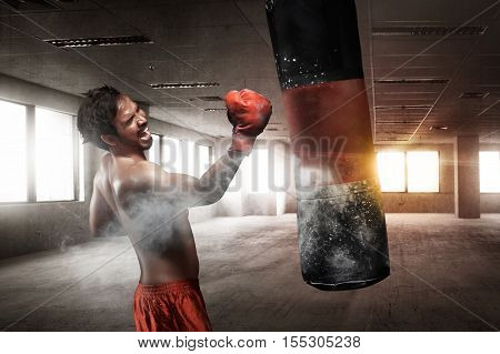 Powerful Asian Male Boxer With Punching Bag