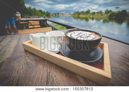 Hot coffee mocha with foam milk art in afternoon break. Coffee mocha on the wood desk with natural outdoor.(vintage effect)