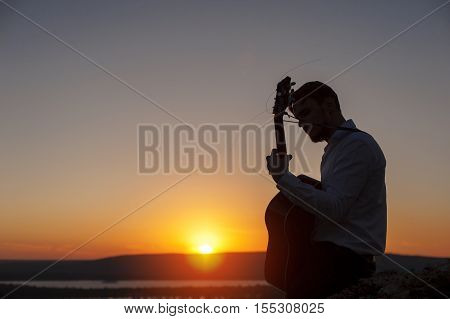 Young lonely guitarist playing on acoustic guitar on the evening beach and sundown