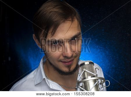 Portrait of youn attractive singer standing behind microphone at the background of spotlight.