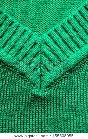 Closeup of knitted woolen fabric texture. Emerald knitwear