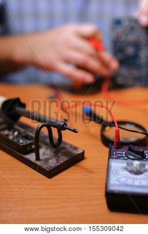 Eletrician checking board by multimeter. Closeup of male hands soldering iron on the table. Man repairing computer components.