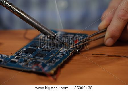 Closeup of male hands with soldering iron and tweezers. Electrician repairing computer board.