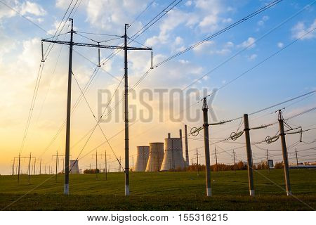 Industrial landscape with heat electro-power station of cogeneration type with chimneys and cooling towers in background and pylons for high voltage electricity distribution in foreground at sunset