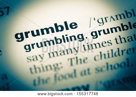 Close Up Of Old English Dictionary Page With Word Grumble