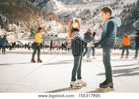 Happy children ice skating at ice rink outdoor, figure skating, at winter day, sport and healthy lifestyle, ice skating at Holland. Funny kids, boy and girl, sister and brother. Family