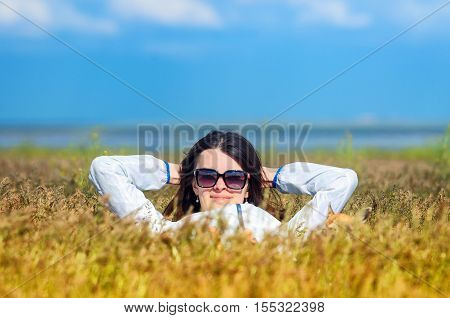 A sexy attractive girl wears the white clothes lies in a field and looks to camera. Her hands behind her head. Young woman wears sunglasses relaxing laying on yellow grass of Astrakhan steppe near the Baskunchak salt lake. She is smiling fron to camera
