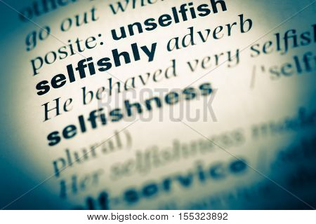 Close Up Of Old English Dictionary Page With Word Selfishly