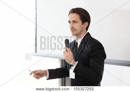 Speaker with microphone at business conference on whiteboard background