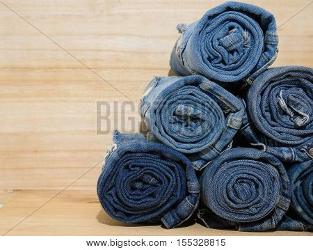 Rolled jeans stack on wooden board