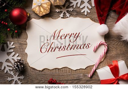 High angle view of Santa Claus letter with Merry Christmas text on it. Top view of merry Christmas xmas wish list with little gift present and santa claus hat on wooden background.