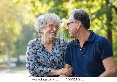 Portrait of a senior couple smiling and looking each other at park. Happy old man and woman sitting outdoor. Loving senior couple relaxing at park.