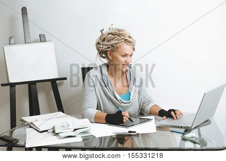 Portrait of smiling designer working on graphics tablet against wooden easel with clean paper and art supplies in room