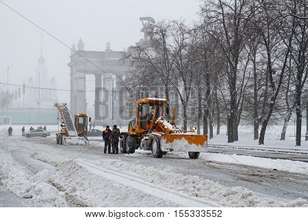Moscow Russia - January 13 2016: Workers clean from the road snow near the entrance to VDNKh in Moscow
