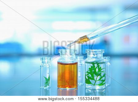 three glass vials with green leaf with orange solution drop in the lab science