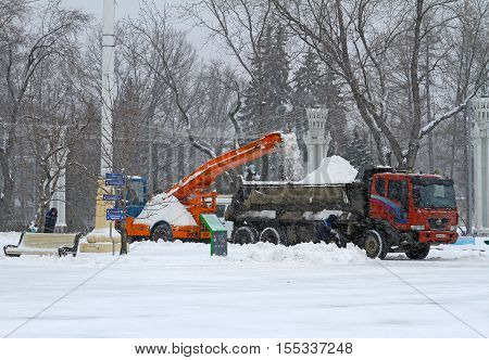 Moscow Russia - January 13 2016: Workers clean from the road snow in VDNKh in Moscow