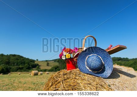 Bouquet garden flowers picnic basket and summer hat on hay roll in summertime in France