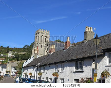 Parish church and Main Street in Beer Village centre Devon England UK GB EU Europe