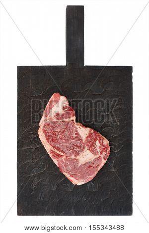 Raw rib-eye steak on black cutting board, isolated on white