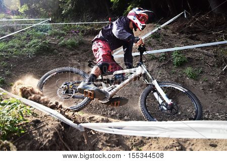 Sport race Mountain biker extreme and fun downhill track. Dirt splash. Focus on the biker, defocus on the dirt