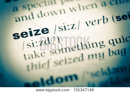 Close Up Of Old English Dictionary Page With Word Seize