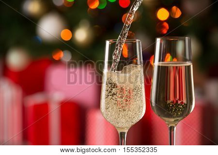 Glasses of wine and christmas gifts on the bright background