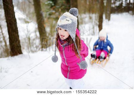 Two Adorable Little Sisters Enjoying Sleight Ride On Winter Day