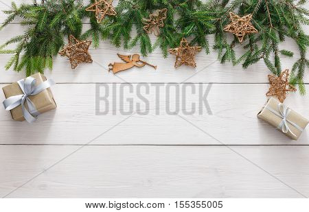Christmas decoration, gift boxes, garland and angel figure frame background, top view with copy space on white wood table surface. Christmas ornaments and presents border