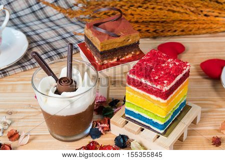 A piece of chocolate pie rainbow cake and a cup of chocolate mousse on wooden backdrop with selective focus