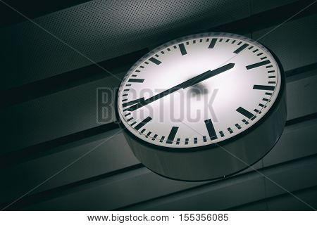 A white clock is hanging down from the ceiling
