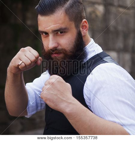 Angry bearded young businessman hipster standing in boxer position and ready to fight looking at camera