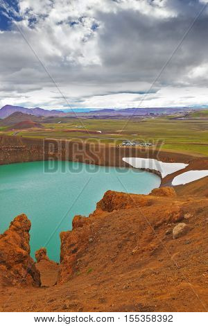 Picturesque lake in the crater of an extinct volcano. Lake water bright green color. On the shores lie snowfields from last year. Summer in Iceland