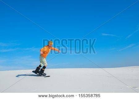 Sand boarder slides down the of the sand dune. Sand boarding in desert in the sunny day. Preparation for winter season snowboarding.