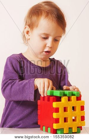 little cute girl playing indoors (developmental toys for children)
