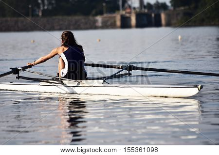 Scull rowing team training at a dam