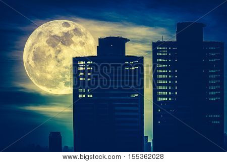 Silhouettes Of Two Skyscrapers Construction With Background Of A Large Moon At Nighttime. Cross Proc