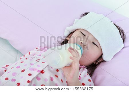 Closeup sick asian girl with cold and flu sucking up milk bottle and lying in bed. Drinking milk for good health.
