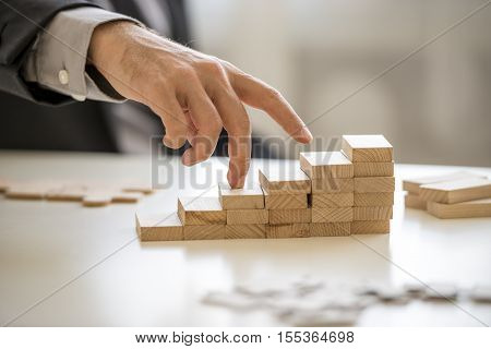 Fingers walking up blocks as stairs for concept about business and climbing up in seniority.