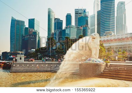 SINGAPORE - SEPTEMBER 4: The Merlion statue in front of skyscrapes in tourist popular bay in Singapore on September 42014. Statue of a lion's head and fish body is a symbol of Singapore.