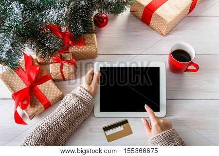 Christmas online shopping top view on wood. Female buyer touch screen of tablet, copy space. Woman has coffee, buys presents for xmas eve, among gift boxes. Winter holidays sales background