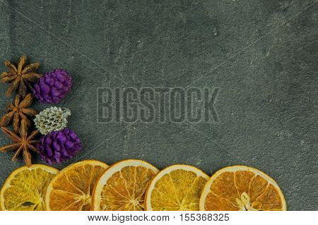 Christmas and New Year decoration with dried slices of orange star anise and colored cones with space for text on the right an old stone kitchen counter. Top flat horizontal view.