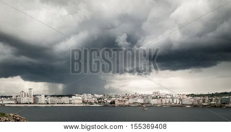 Heavy storm with rain and dramatic clouds over the city center of A Coruna Northern Spain - Atlantic Ocean. Dark clouds with loads of heavy rain visible.