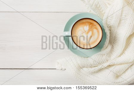 Winter cappuccino composition. Blue coffee cup top view with foam and knitted sweater at white wood background with copy space. Warming hot drinks concept