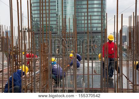 Bangkok, Thailand - November 10 2008 :  In a construction site in Bangkok, women and men work on metal structure. Salaries are very low for a dangerous and tiring work. Most workers come from the north east of Thailand, Cambodia and Myanmar.